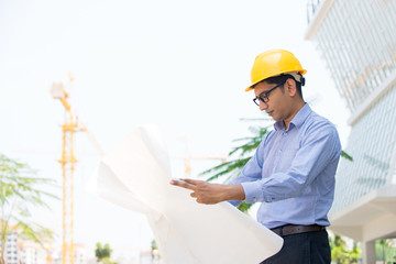 indian architect reading plans on construction site