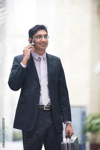 asian indian business male on a phone with suit case