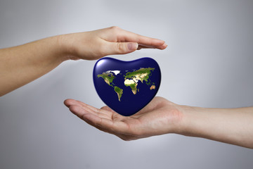 Earth in shape of heart in a female and male hands.