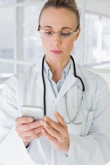 Female doctor reading text message in hospital
