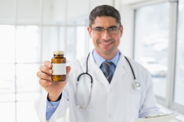 Smiling male doctor with a bottle of pills in hospital