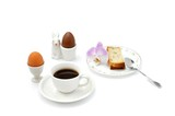 Orchid flower, cup of black coffee with egg cups