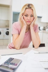 Worried woman with bills and calculator in kitchen