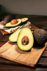 Ripe halved avocado on wooden cutting board. Closeup.
