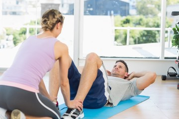 Trainer assisting fit man in doing sits