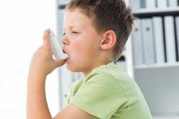 Boy using an asthma inhaler in clinic