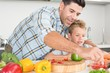 Handsome father showing his son how to prepare vegetables