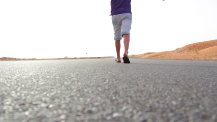 a young man walking along the road in the desert