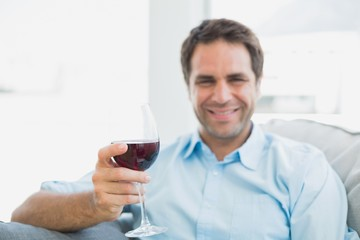 Cheerful man relaxing on sofa with glass of red wine