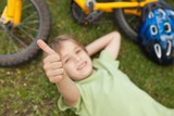 Relaxed boy gesturing thumbs up at park
