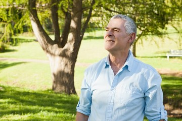 Thoughtful mature man looking away at park