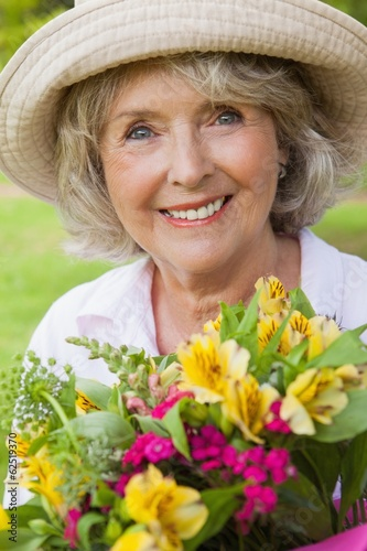 Close-up of a smiling mature woman holding flowers at park