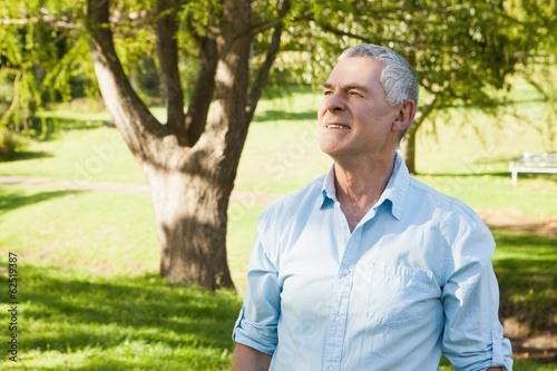 Thoughtful mature man looking away at park
