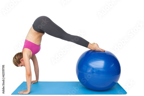 Side view of a fit young woman stretching on fitness ball