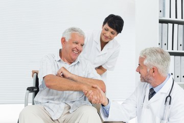 Happy senior patient and doctor shaking hands