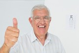 Smiling senior man gesturing thumbs up with eye chart in