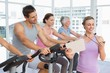 Trainer besides people working out at spinning class