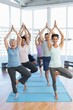 Class standing in tree pose at yoga class