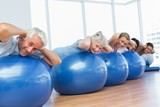 Sporty people stretching on exercise balls in gym