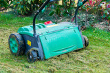 lawn aerator removing moss from garden.