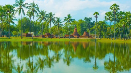 Thailand, Sukhothai - Park with a pond, palm trees and ruins
