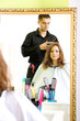 Young man hairdresser makes hairstyle girl in beauty salon