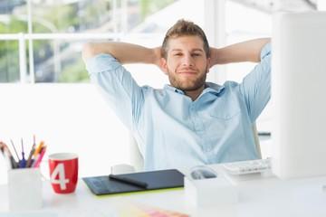 Designer relaxing at his desk smiling at camera