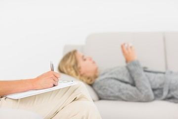 Therapist taking notes on her patient on the sofa