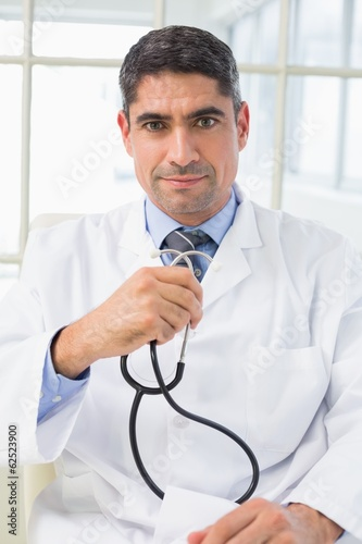 Serious male doctor holding stethoscope