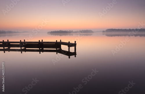 Fototapeta Jetty during a tranquil, foggy dawn at a lake.