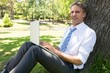Businessman with laptop leaning on tree