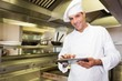 Smiling male cook using digital tablet in kitchen