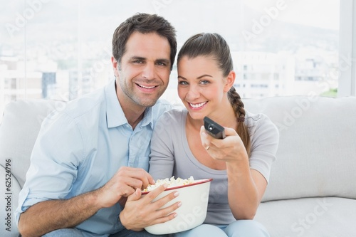 Smiling couple watching tv on the couch with bowl of popcorn