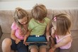 Three kids using digital tablet in living room