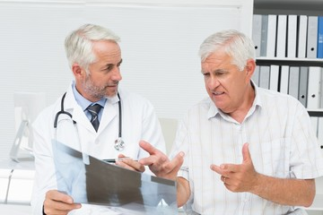 Male doctor explaining x-ray report to senior patient
