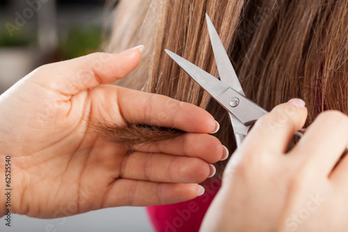Hairdresser cutting woman's hair