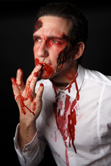 Psychopath licking blood from his fingers