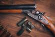 Shotgun with shells on wooden background - 62526963