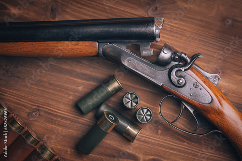 Leinwanddruck Bild Shotgun with shells on wooden background