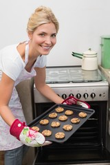 Smiling woman putting a tray of cookies in oven