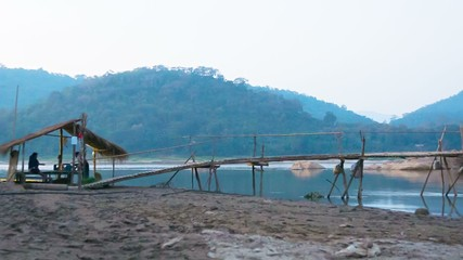 Old wooden bridge on the river. Laos, Luang Prabang, evening