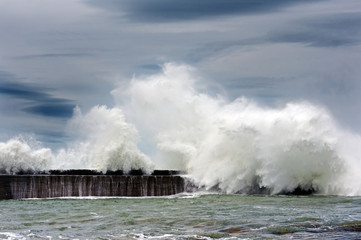 big waves breaking on breakwater