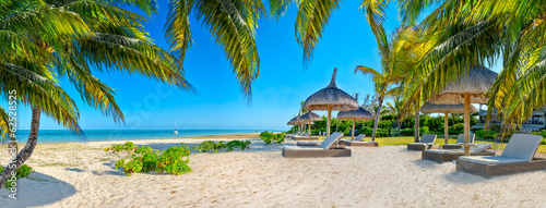 Paradise beach with palms and parasol