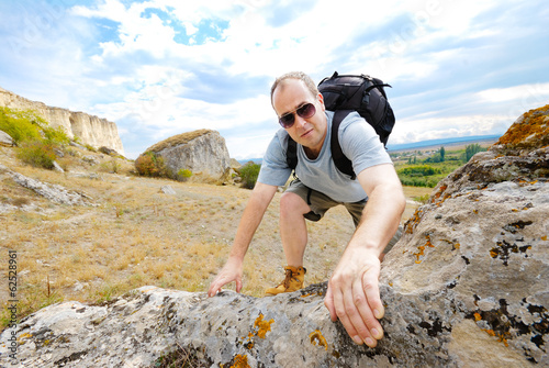 Adult man is climbing a mountain