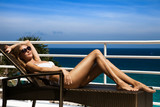 Young woman lie on sunbed and sunbathing. Luxury sea view.