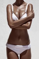 Beautiful tan female model. Against white wall.