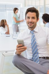 Smiling businessman text messaging with colleagues at office