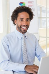 Smiling businessman using laptop at office desk