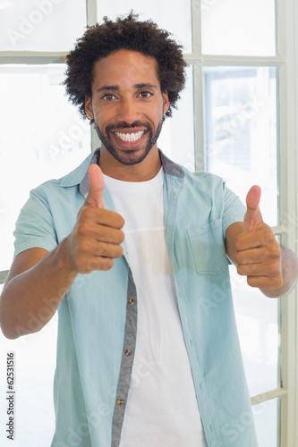 Smiling casual businessman gesturing thumbs up in office