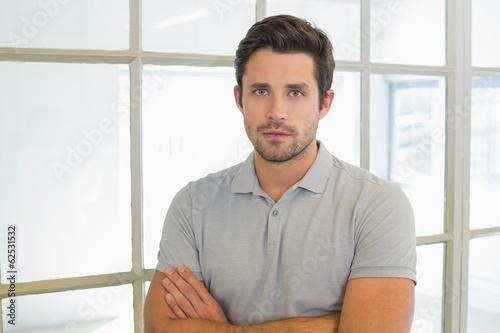 Serious casual businessman with arms crossed in office